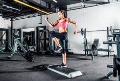 Woman exercising in gym. Young sportive woman exercising in gym using step platform Stock Photography
