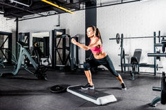 Woman exercising in gym. Young sportive woman exercising in gym using step platform Royalty Free Stock Photo