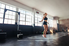 Woman exercising in gym. Young woman exercising using skipping rope in gym. Athletic woman training hard at the gym Stock Photography