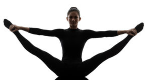 Woman exercising gymnastic yoga  stretching split. One caucasian woman practicing gymnastic yoga stretching split in silhouette  on white background Stock Photography