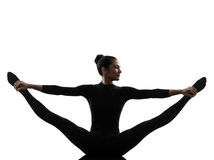 Woman exercising gymnastic yoga  stretching split  silhouette Royalty Free Stock Images
