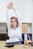 Woman exercising her back in office Royalty Free Stock Photos