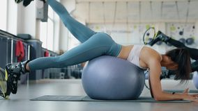 Woman exercising her legs in fitness center. Woman exercising her legs with fitball in fitness center stock video footage