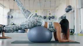 Woman exercising her legs in fitness center. Woman exercising her legs with fitball in fitness center stock footage