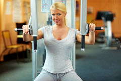 Woman exercising her muscles. Happy woman in a gym exercising her muscles Royalty Free Stock Image