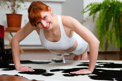 Woman is exercising at home Royalty Free Stock Photos