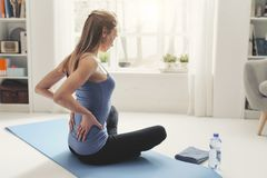 Woman exercising at home and stretching her back. Woman exercising at home, she is sitting on the floor and stretching her back, fitness and wellness concept stock photo