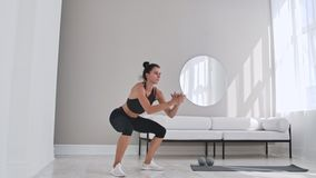 Woman exercising jumping squats in home. Healthy female in sportswear doing jumping squats at home. Woman exercising at. Living room stock video footage