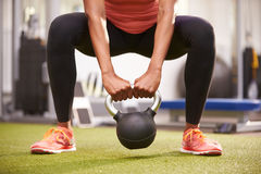 Woman exercising with a kettlebell weight, front view low-section crop Stock Photos