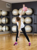 Woman Exercising While Lifting Kettlebell On Hardwood Floor At G Stock Photos