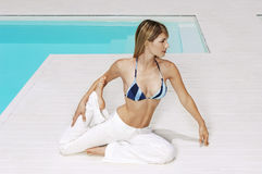 Woman Exercising While Looking Away At Poolside Royalty Free Stock Image