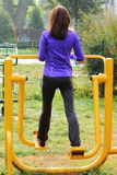 Woman exercising lower body on outdoor gym, healthy lifestyle Stock Images