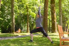 Woman exercising in a lush green spring park. Working out doing stretching exercises amongst the trees in a side view Stock Images