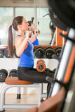 Woman exercising on machine for bodybuilding Royalty Free Stock Images