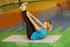 Woman exercising on mat in fitness class. Female workout. Pilates abs legs up Royalty Free Stock Image