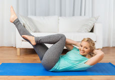 Woman exercising on mat at home Stock Image