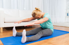 Woman exercising on mat at home Stock Photo