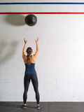 Woman exercising with the medicine ball. Photo of a woman exercising by throwing a medicine ball up against a wall in a gym Royalty Free Stock Photo