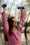 Woman Exercising in the Nature. Young woman with weights exercising in the nature Healthy lifestyle and fitness concept Stock Image
