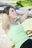 Woman exercising outdoors. Doing abdominal workout Royalty Free Stock Images