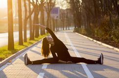Woman exercising outdoors. Woman doing stretches or yoga outdoors on brick pedestrian path stock photography