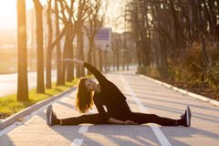 Woman exercising outdoors. Woman doing stretches or yoga outdoors on brick pedestrian path Royalty Free Stock Photography