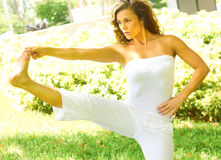 Woman Exercising In Park. Beautiful young woman touching toes while standing on one leg. Horizontal shot Stock Photo