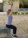 Woman exercising in park doing her stretches outdoor. Stock Photo