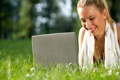 Woman after exercising in the park resting and using laptop Stock Photos