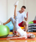 Woman exercising with personal trainer Stock Photo