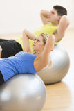 Woman Exercising On Pilate With Man In Background At Club Royalty Free Stock Photography