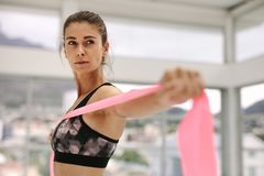 Woman exercising with a resistance band. Caucasian woman exercising with a resistance band. Young fitness female training using a resistance band indoors at gym Stock Photography