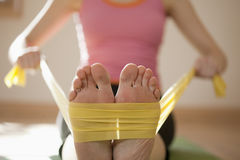 Woman Exercising with Resistance Bands. Woman exercises with resistance bands around her feet. Horizontal shot Royalty Free Stock Photo