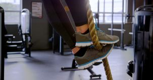 Woman exercising with rope in fitness studio 4k stock video footage