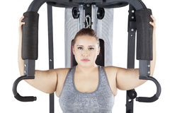 Woman exercising on a shoulder press machine. Image of obese female looking at the camera while exercising on a shoulder press machine in the studio royalty free stock image