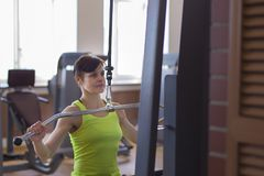 Woman exercising on the simulator doing strength exercises stock images