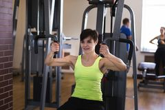 Woman exercising on the simulator doing strength exercises stock image