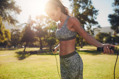 Woman exercising with skipping rope outdoors Stock Photo