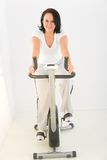 Woman exercising on spinning bike Stock Images