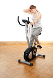 Woman exercising on stationary bicycle Stock Photography