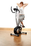 Woman exercising on stationary bicycle Stock Images