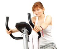 Woman exercising on stationary bicycle Stock Image