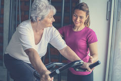 Woman exercising on stationary bikes in fitness class. Wo. Senior women exercising on stationary bikes in fitness class. Woman workout in gym. Senior with Stock Photography