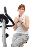 Woman exercising on stationary training bicycle Royalty Free Stock Image