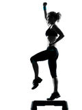Woman exercising step aerobics Stock Images