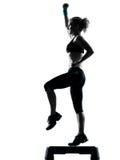 Woman exercising step aerobics Stock Images
