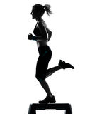 Woman exercising step aerobics Royalty Free Stock Photography