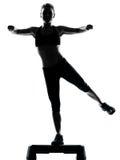 Woman exercising step aerobics Stock Image