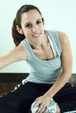 Woman Exercising and Stretching. Woman exercising her stretching next to the window. Natural sunlight provides lighting Royalty Free Stock Images