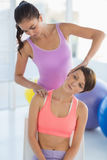 Woman exercising with trainer. Young women exercising with trainer at fitness studio Royalty Free Stock Photos